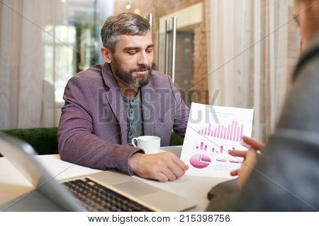 Handsome bearded white collar worker sitting at cafe table and analyzing financial figures with male colleague, he holding document with diagrams and charts in hand