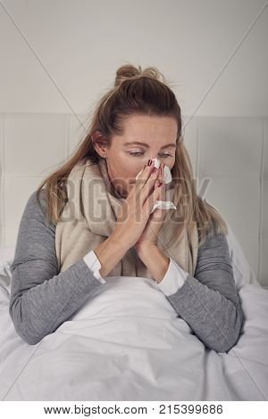 Sick woman with seasonal cold and flu lying wrapped up warmly in bed with a miserable expression blowing her nose on a tissue