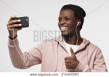 Photo Of Handsome Black Male Isolated On Grey Background, Stretching Arm With Smartphone To Take Sel