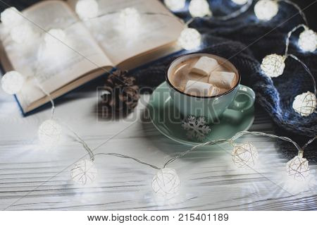 Cozy winter home. Cup of cocoa with marshmallows warm knitted sweater open book Christmas garland lump on a white wooden table. Atmosphere of a pleasant evening for reading.