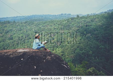 Asian man travel relax in the holiday. seats relax read book on rocky cliffs. On the Moutain. In Thailand