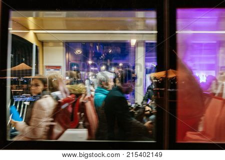 STRASBOURG FRANCE - NOV 21 2017: Defocused in motion commuters tourists and locals inside tramway late in the evening in Strasbourg with reflection of the Place Kleber square