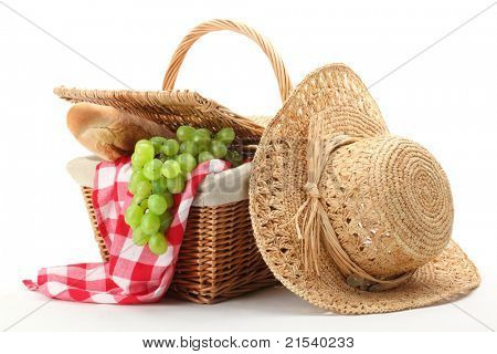 Picnic basket and straw hat isolated on white background.