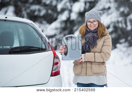 Woman driver standing next to car on a background of snow-covered winter forest. Snowy weather. Woman holds the jerry can with automotive oil in her hands and smiling. Car maintenance for the winter.