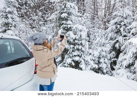 Young woman takes photo of snow-covered winter forest. Snowy weather. Woman taking photo on phone. Girl smiling at the camera. Winter holidays.