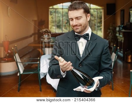 Smiling Cheerful Waiter With A Bottle Of Champagne
