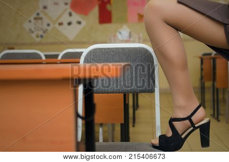 Sexy female feet in high heels shoes and pantyhose stockings standing on school chair on classroom background.