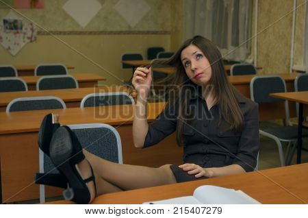 Wistful female student in a high heels shoes sits carefree on chair at her school desk with her legs folded over her and smiles and dreaming.