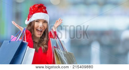 Christmas Shopping. Attractive Happy Girl With Credit Card And Shopping Bags In Santa Hat
