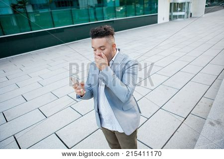 Portrait of young astounded businessman standing outside, closing his mouth with hand, holding smartphone and looking at screen. Man shocked with news. Good or bad news concept