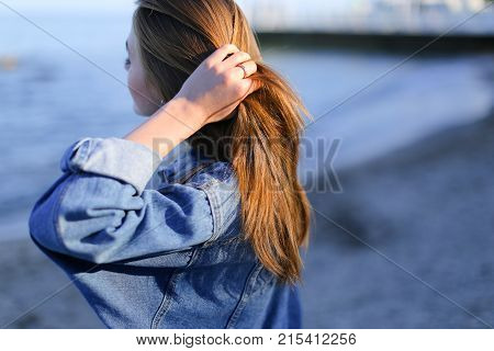 Joyful woman rests from bustle of city, standing with back to camera on shore of endless sea. Young woman rejoices, raises hands up