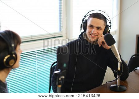 Cute female radio host and funny guy with headphones and talking are direct inclusion of radio, sitting in chair in radio studio. In office ponoramic large windows on desktop are microphones and mixing consoles, broadcast processor, special devices and co