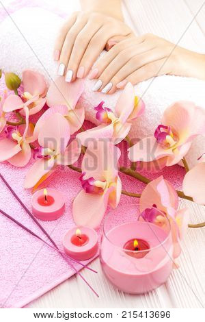 beautiful pink manicure with decor, orchid, towel and candle on the white wooden table. spa