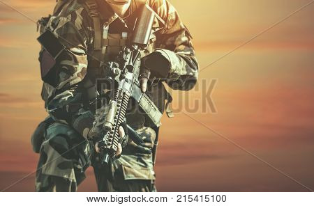 The soldier in the performance of tasks in camouflage and protective gloves holding a gun against the background of sunset. War Zone.