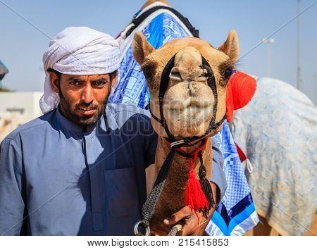 Dubai, United Arab Emirates - March 25, 2016: Camel handler with his animal at Dubai Camel Racing Club