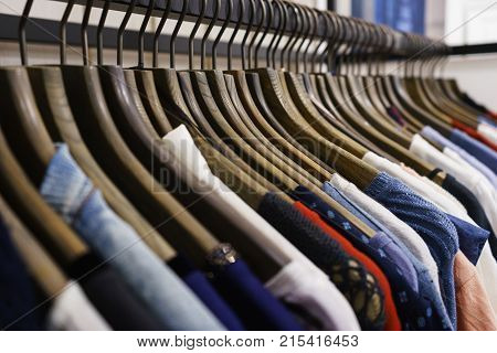 Modern clothes in a shop on a hanger. Shirts and sweaters of different colors and denim for youth. Clothes of different styles on the hanger in the showroom. Soft focus.