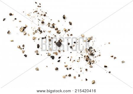 Crushed black peppercorns scattered on white background.