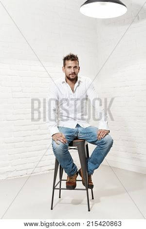 Full length indoor portrait of handsome man in casual cloth sitting on barstool.
