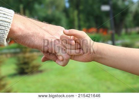 Senior man and his grandchild making pinky promise on blurred background