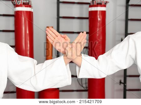 Hands of young man and woman practicing karate in dojo