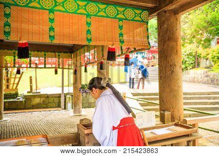 Nara, Japan - April 26, 2017: back of Shinto Miko, a maiden or a supplementary priestess inside main sanctuary of Kasuga Taisha in Nara. The miko's attire consists of a white haori and a red hakama.