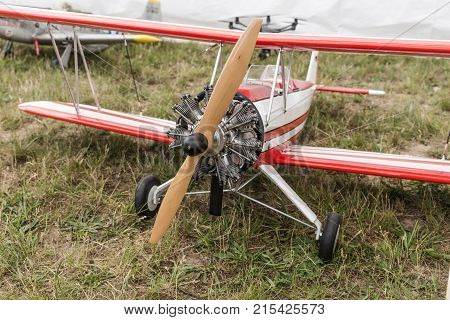 Red white model airplane on the meadow