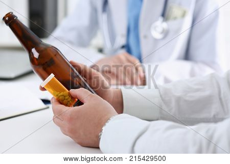 Alcoholic hold in hand empty bottle at doctor reception office closeup. Grief and despair intoxicated change life drunkenness lifestyle sobriety and temperance bad habit dependence concept
