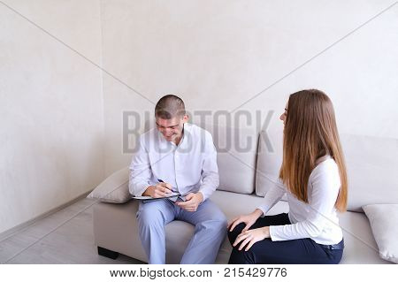 Charming girl tells about medical history of male psychiatrist with friendly smile on face, listens and writes with pen to medical card and prescribes course of treatment sitting on light sofa in hospital's office on background of light gray wall in morni