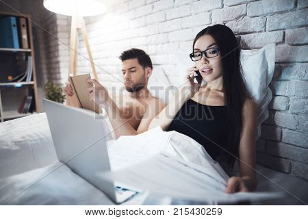 Girl and guy are in bed. The guy reads the book before going to bed. Girl working on laptop in bed. The girl is talking on the phone in bed.