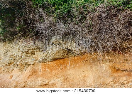 Layers of soil beneath the extreme natural habitat eroded rugged cliff