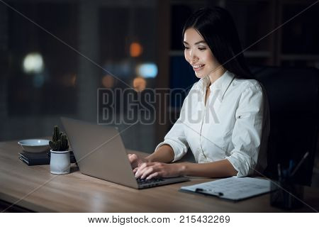 The girl is working late in the dark office with a laptop. Young beautiful businesswoman girl in office.