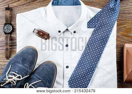 Man's classic clothes outfit flat lay with formal shirt, tie, shoes and accessories. Top view