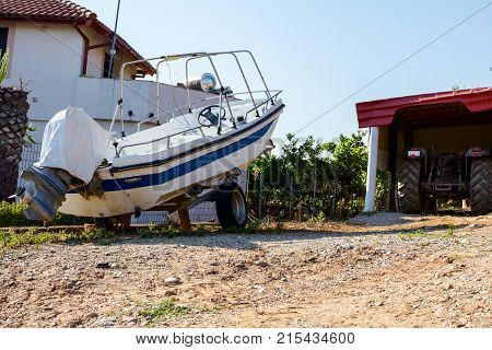 Small motorboat is dry docked on the trailer for transport boats in backyard.