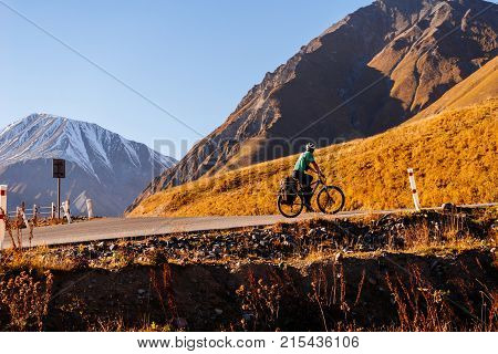 on the background of high Caucasian mountains on the road rides a bicyclist in the helmet
