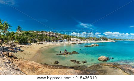 BOWEN, AUS - SEP 18 2017: Horseshoe Bay at Bowen - iconic beach with granite rocks and palm trees, Queensland, Australia