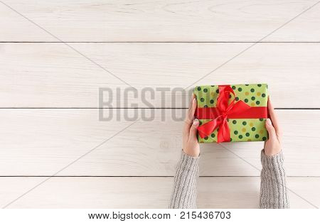 Gift wrapping background. Female hands holding handmade present box in green dotted paper against white wooden table background. Bithday or christmas preparation concept, top view, copy space