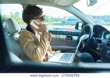 Side view portrait of successful modern entrepreneur using laptop and speaking by smartphone while working in luxury car, copy space