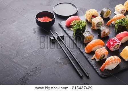 Sushi and rolls background, frame on black, top view. Colorful asian restaurant food set with cutlery, ginger and sauce, traditional japanese cuisine