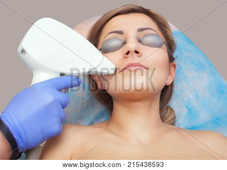 The cosmetologist does the laser hair removal procedure on the face