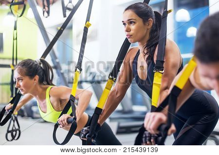 Athlete woman doing push ups with trx fitness straps in the gym Concept workout healthy lifestyle sport