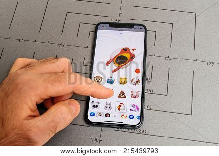 PARIS FRANCE - NOV 9 2017: Man hand selecting singing rooster animoji emoji generated by Face ID facial recognition system with malicious face emotion close-up of the new iphone X 10 Display
