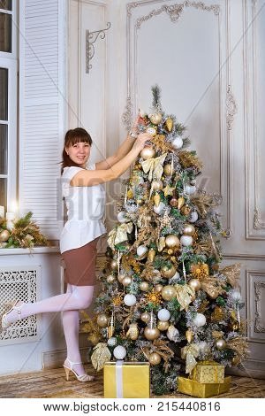 Girl Decorates Christmas Tree In New-year Interior