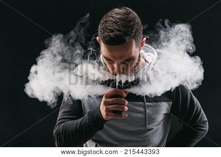 Man with vaping mod exhaling steam at black studio background. Bearded guy smoking e-cigarette to quit tobacco. Vapor and alternative nicotine free smoking concept, copy space