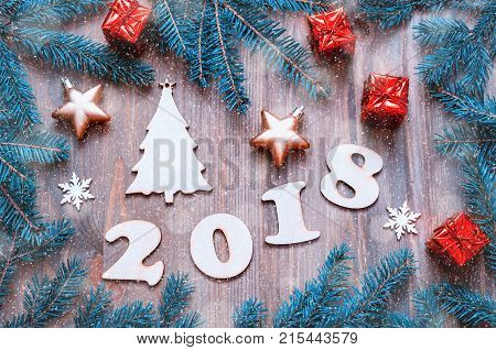 Happy New Year 2018 background with 2018 figures Christmas toys blue fir tree branches. New Year 2018 still life. Festive New Year 2018 composition. Holiday postcard with Happy New Year 2018 concept