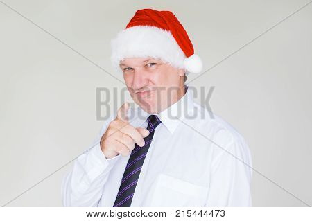 Closeup portrait of smiling middle-aged business man wearing Santa Claus hat, pointing at viewer and looking at camera. Isolated view on white background.