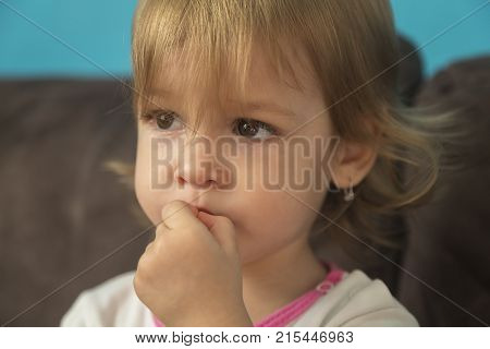 a beautiful little girl looks sad with her fingers in her mouth