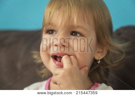 beautiful little girl laughing with his fingers in his mouth