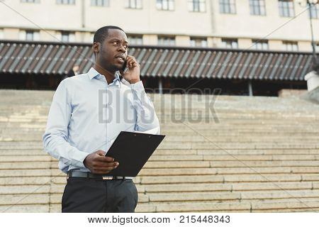 Serious black businessman having tough conversation on smartphone outdoors. Young african-american salesman talking with client, holding notepad near business centre in urban area cityscape