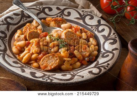 A delicious hearty cassoulet with artisanal sausage tomato bacon and white beans on a rustic tabletop.