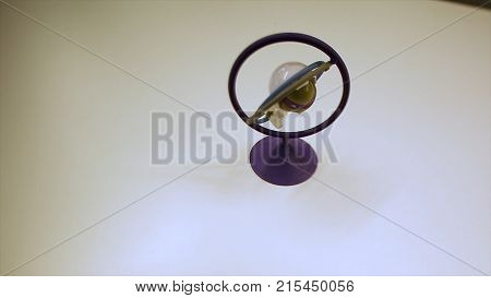 Green gyroscope or toy at white table. Footage. Gyroscopic exercise tool for the prevention of carpal tunnel syndrome HD